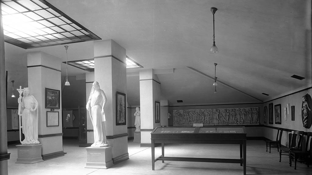 light streaming down on two statues in a historical gallery photo