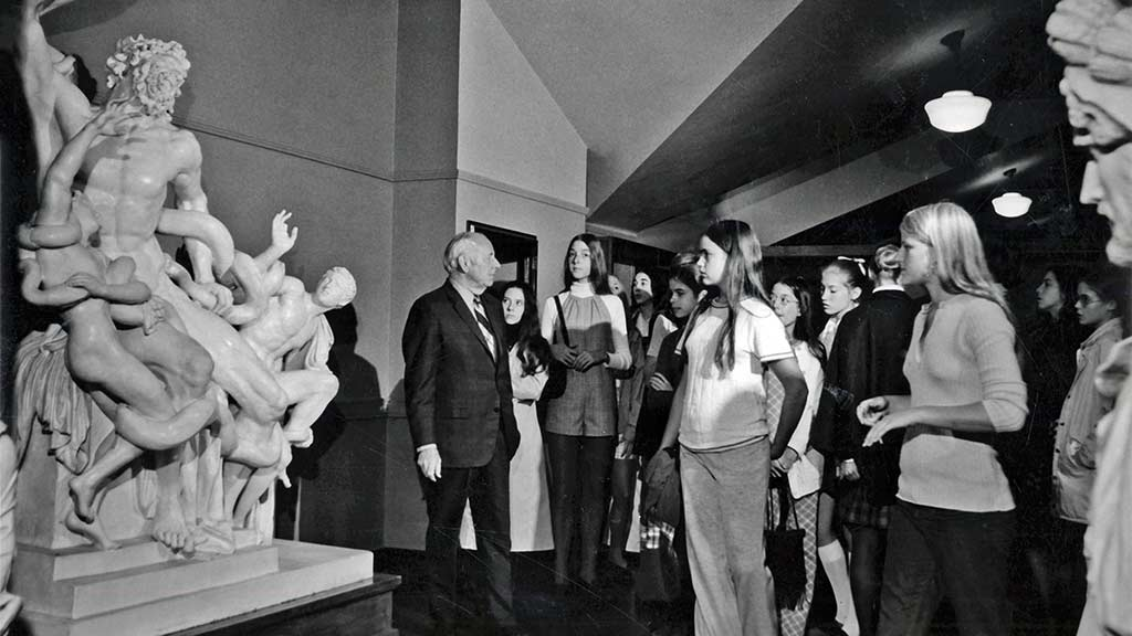 1960's era docent gives a tour to colleges students