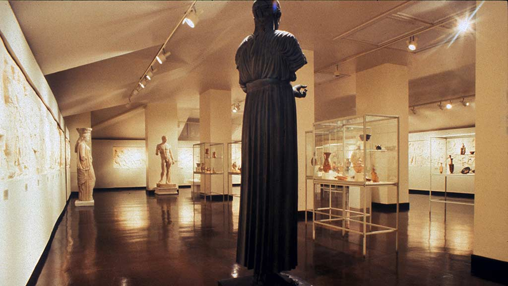 brightly lit gallery of statues and glass cases