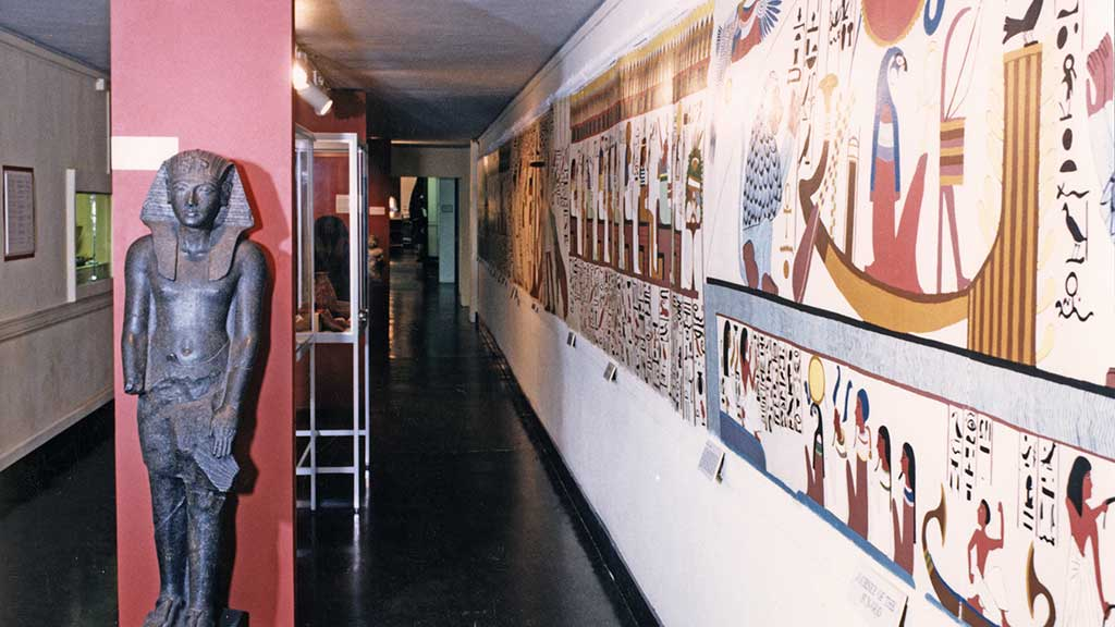 long hallway with an Egyptian statue and mural