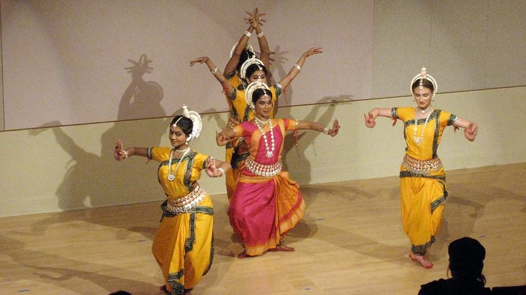 expressive Indian dancers in pink and yellow costumes