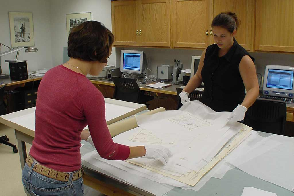 Registration staff measure and document each individual map before it is returned to the Collections Section for storage.