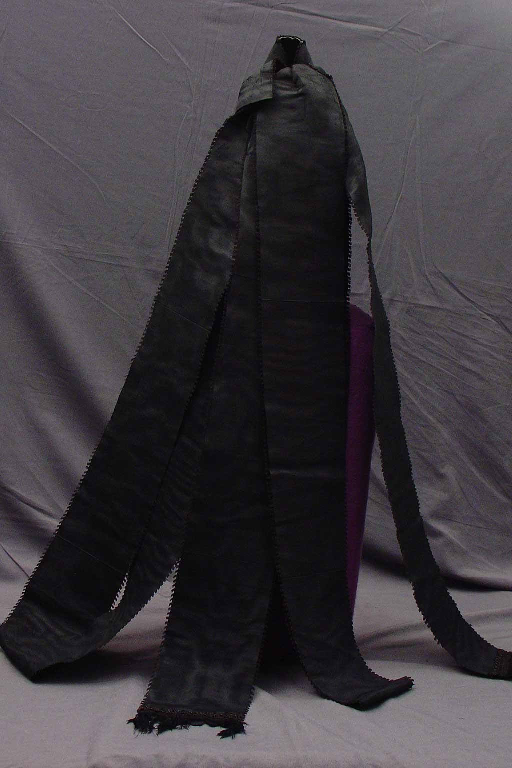 back view, Conical bonnet covered in black silk, with two lengths of the same material doubled and extending down the back.