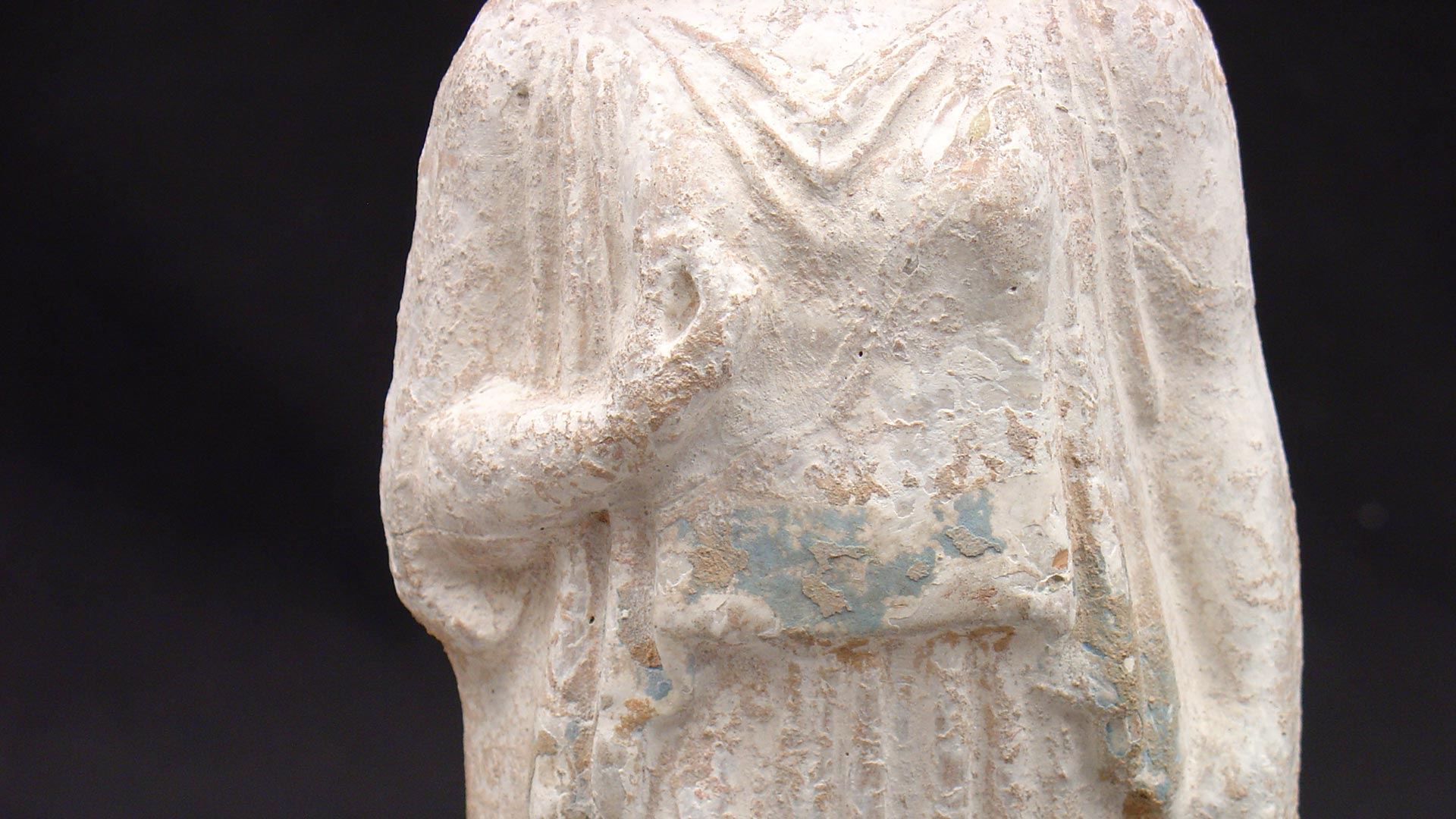 closeup of traces of blue pigment on the torso of the figurine