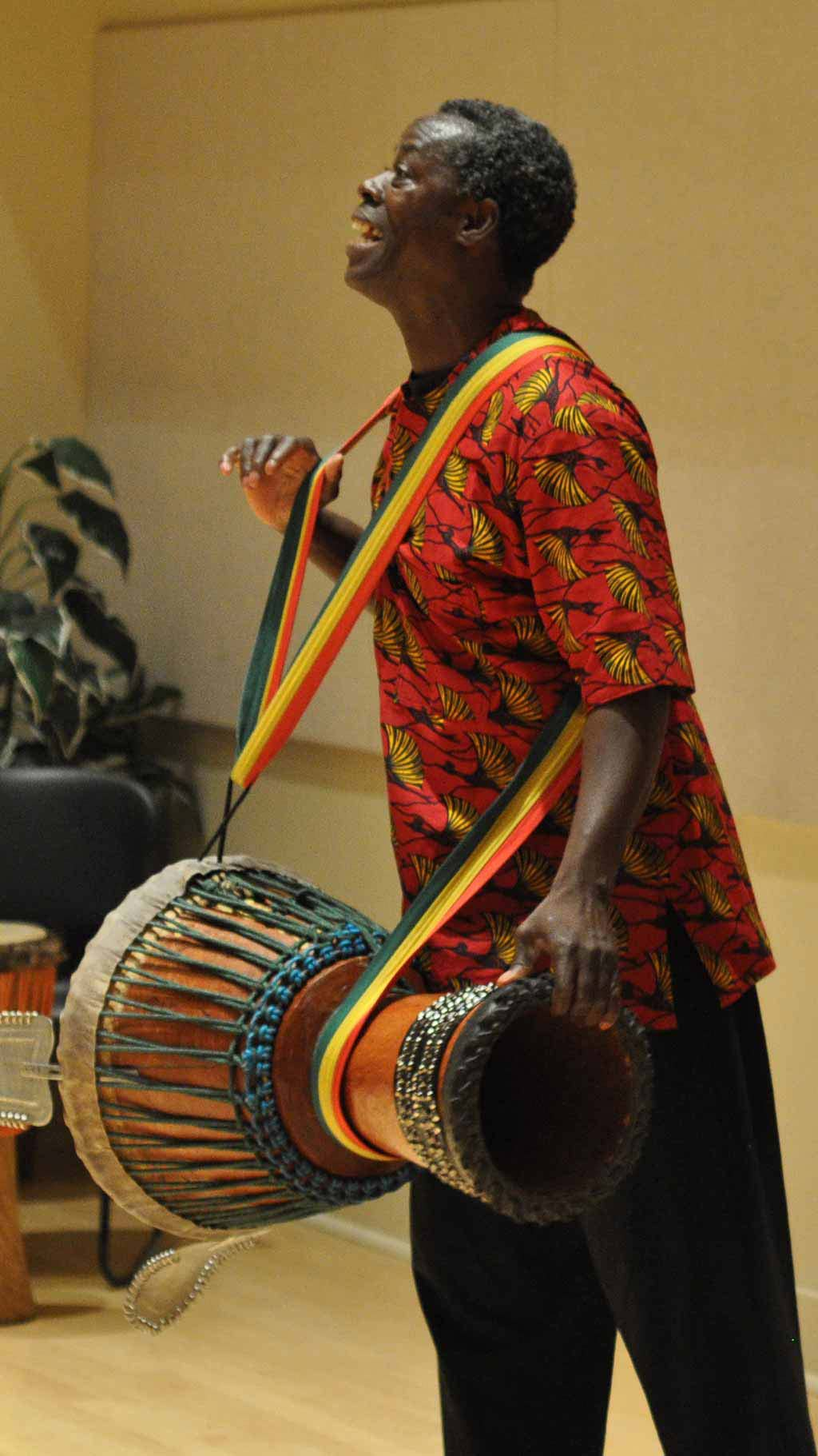 man performing with an African drum