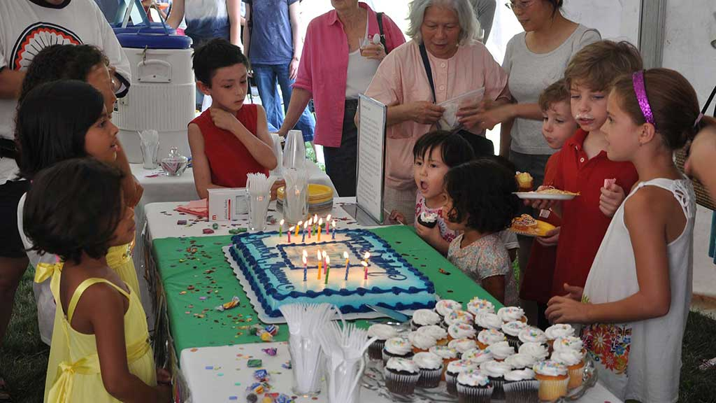 kids gathering around a birthday with lit candles