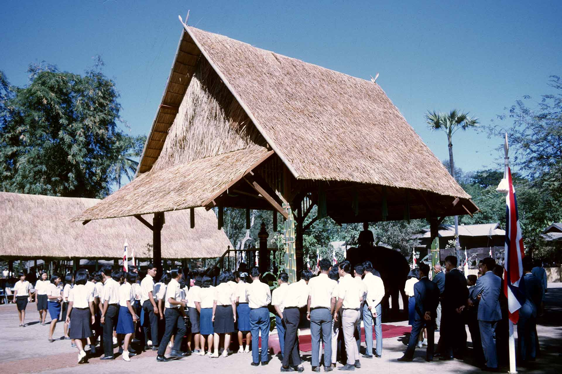 People gather outside a tall wood and straw open-air outbuilding under which is an elephant.