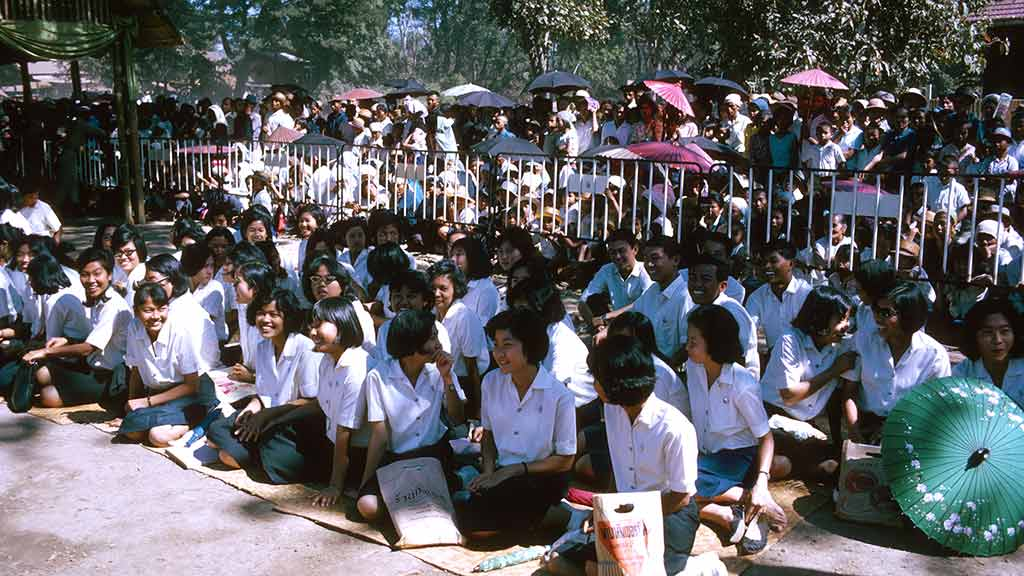 A crowd of uniformed students sits on the ground