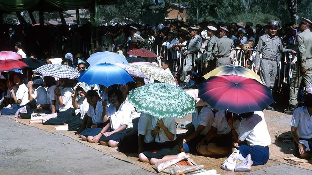 Students shield themselves from the sun with umbrellas