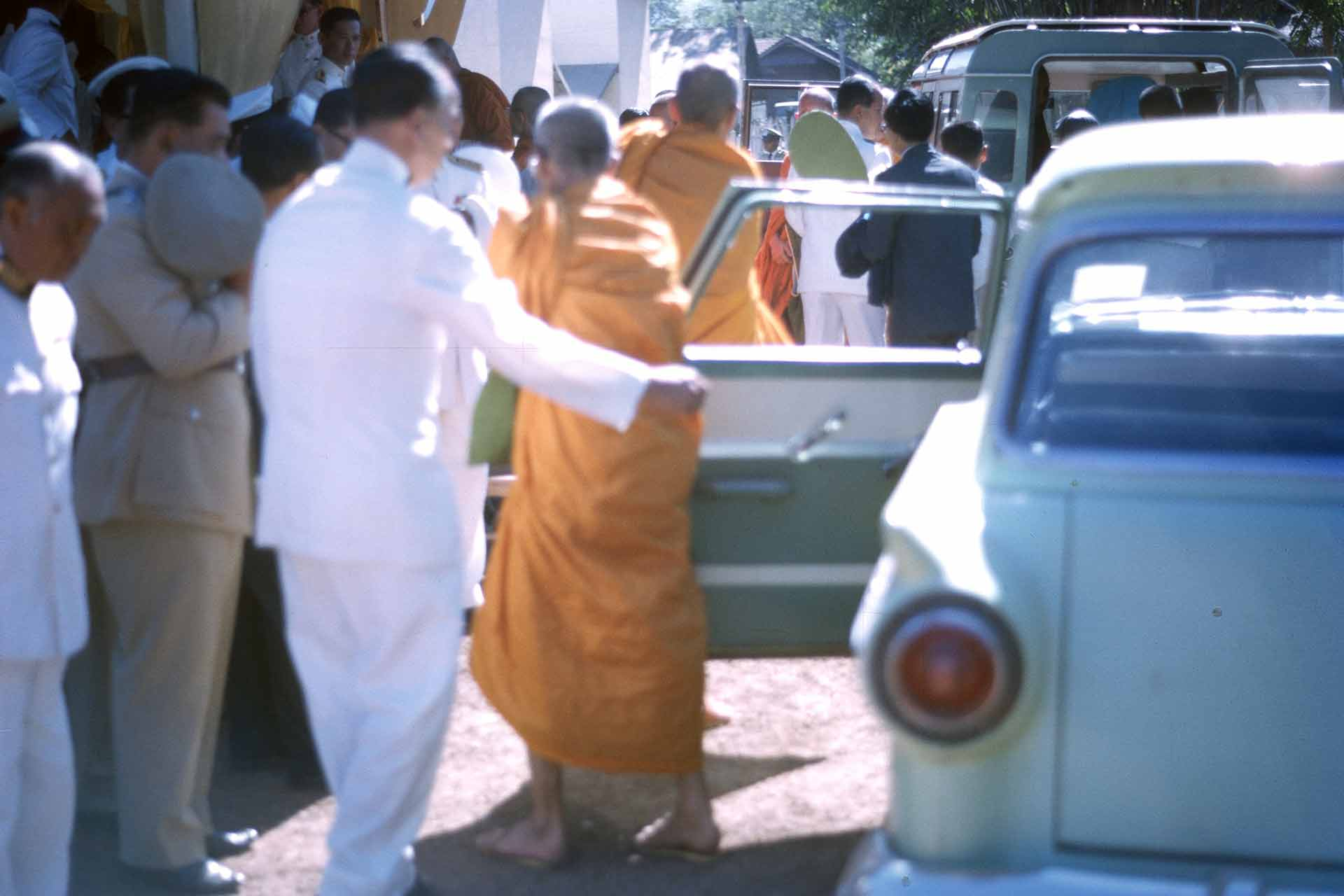 A man and a white suit and a older man in sandals and orange robe emerge from a car