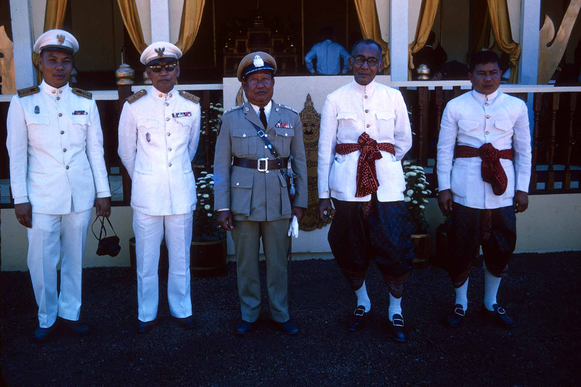 5 men posing. 3 in military uniforms. 2 in white shirts and billowy pants.