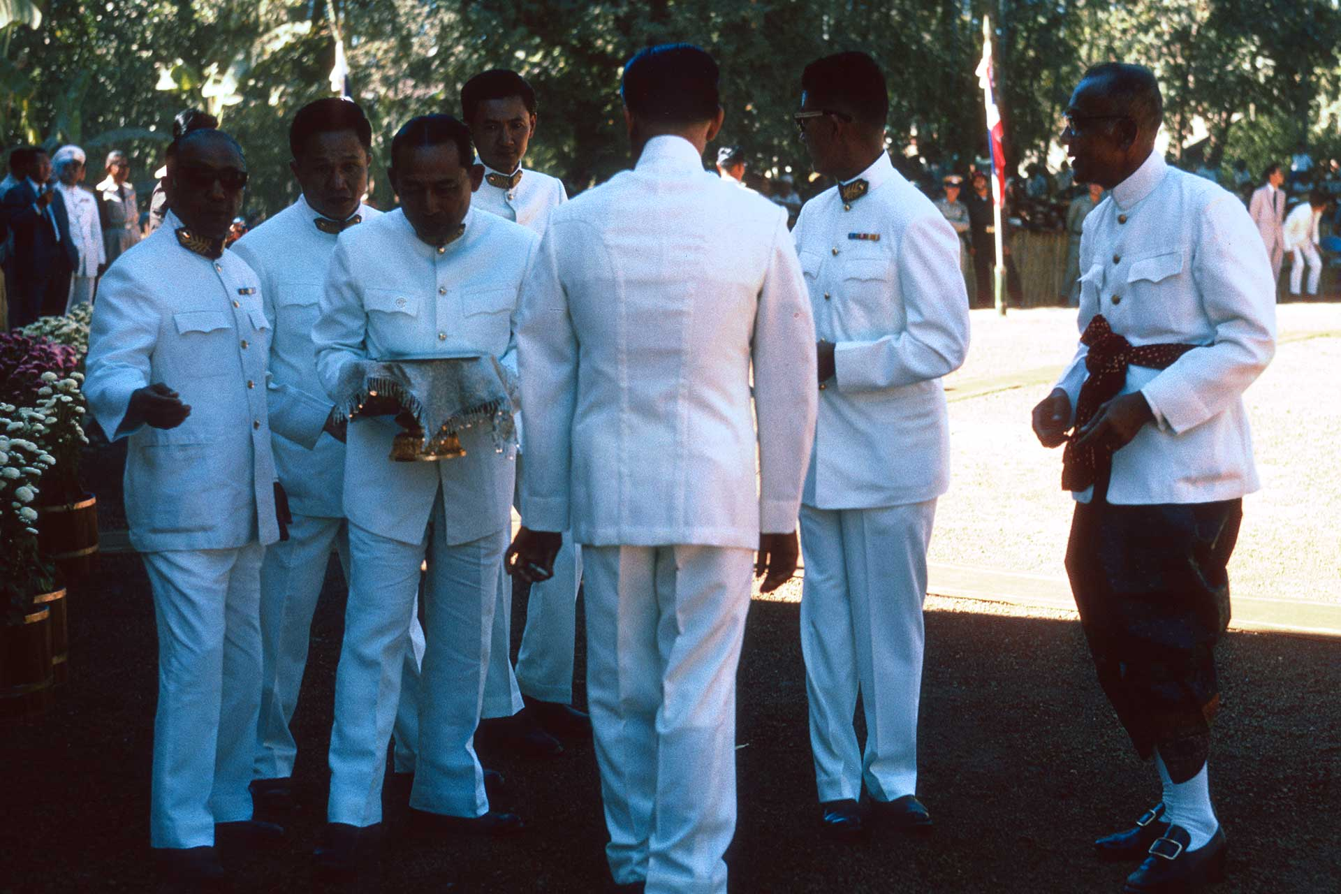 Men in white uniforms carry a ceremonial vessel