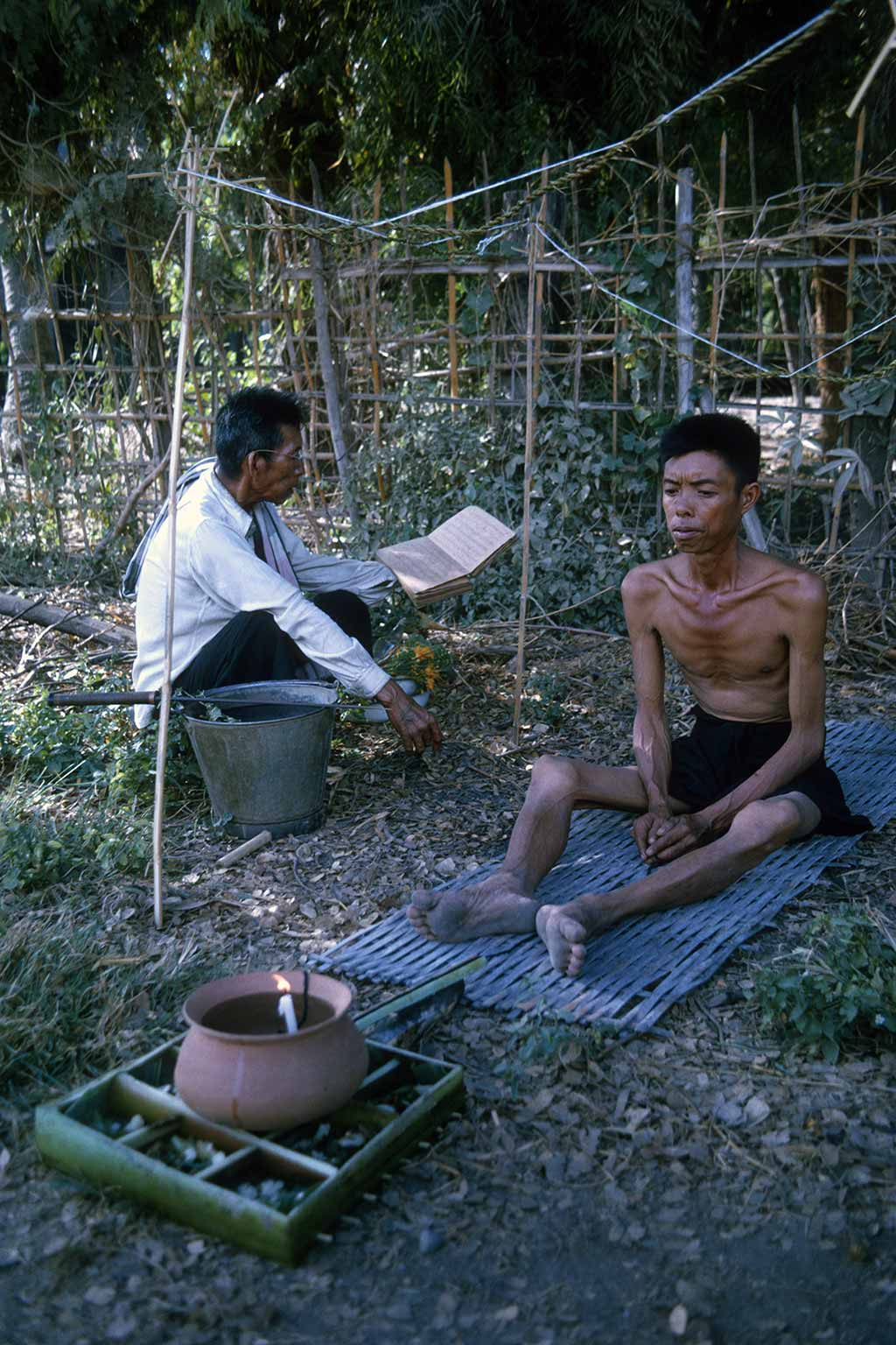 a man in a white shirt reads to a sick man seated outdoors in front of a candle