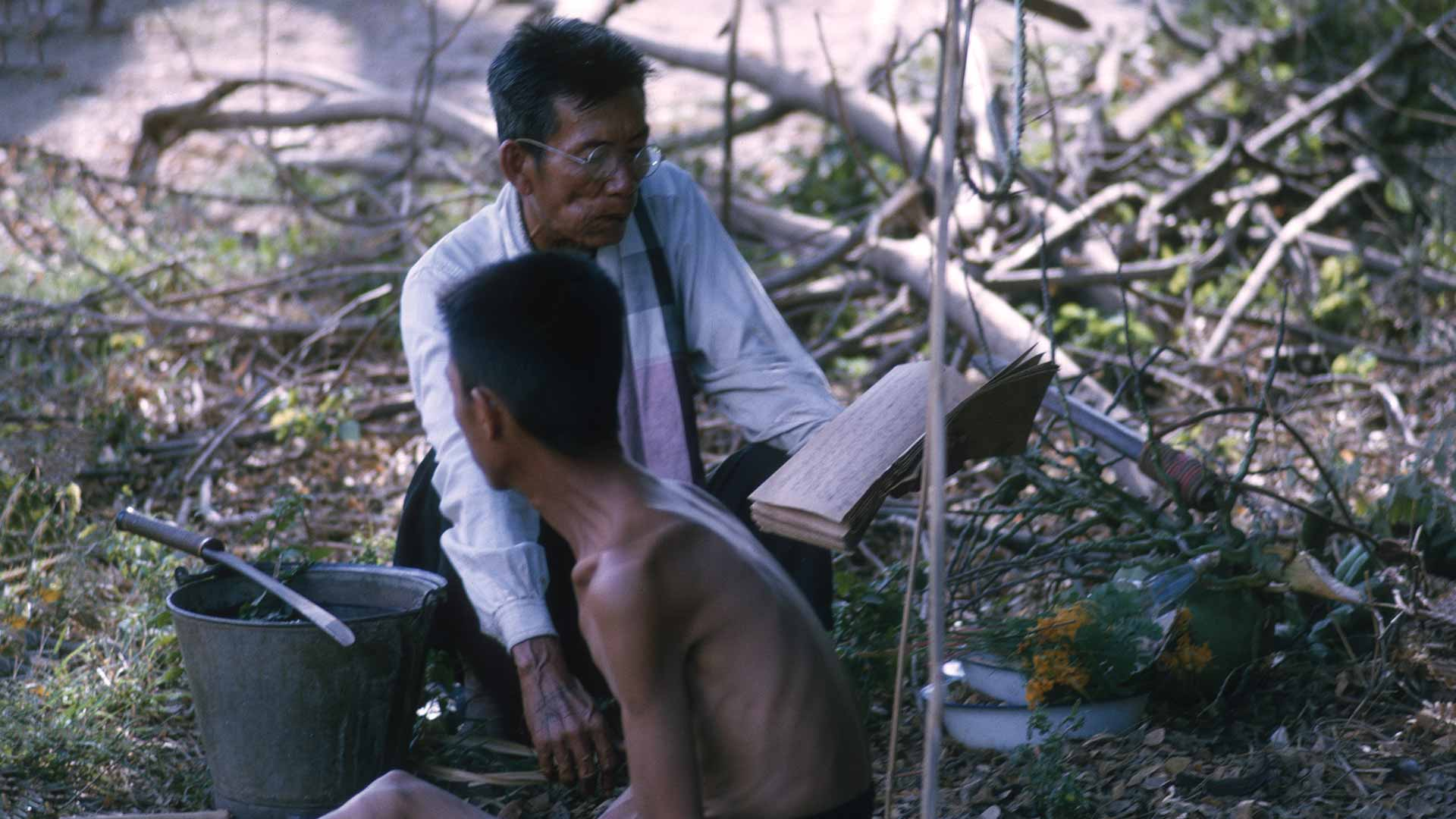 A well dressed man reads from a book to an emaciated shirtless man. Both sit on the ground.