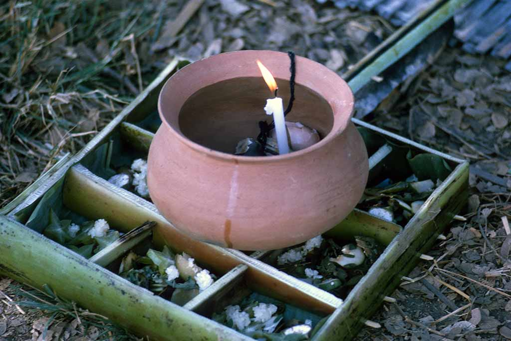 Clay pot on a bamboo frame on the ground. A lit candle and a black string sit inside.