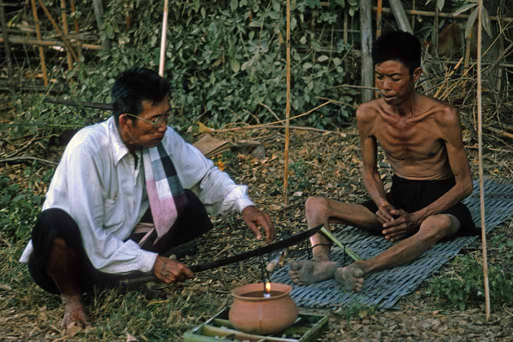A man uses a machete to cut a black string that leads into a clay pot.