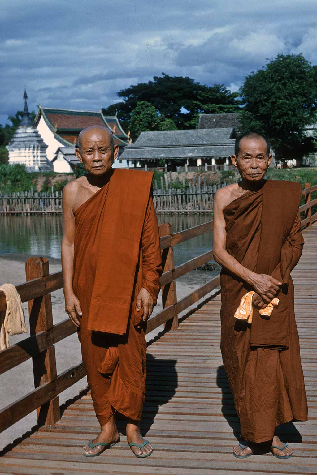 Two monks (orange robe on left, brown robe on right) pose on a bridge in Thailand.