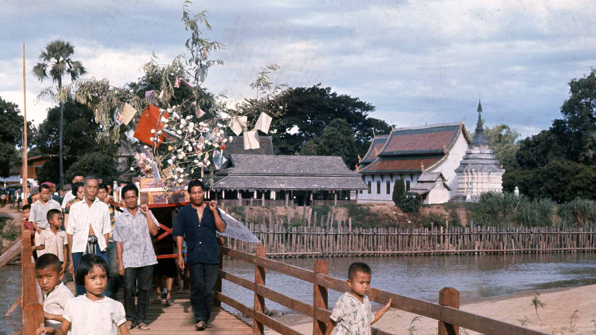 Men carry a large decorated structure using long wood poles