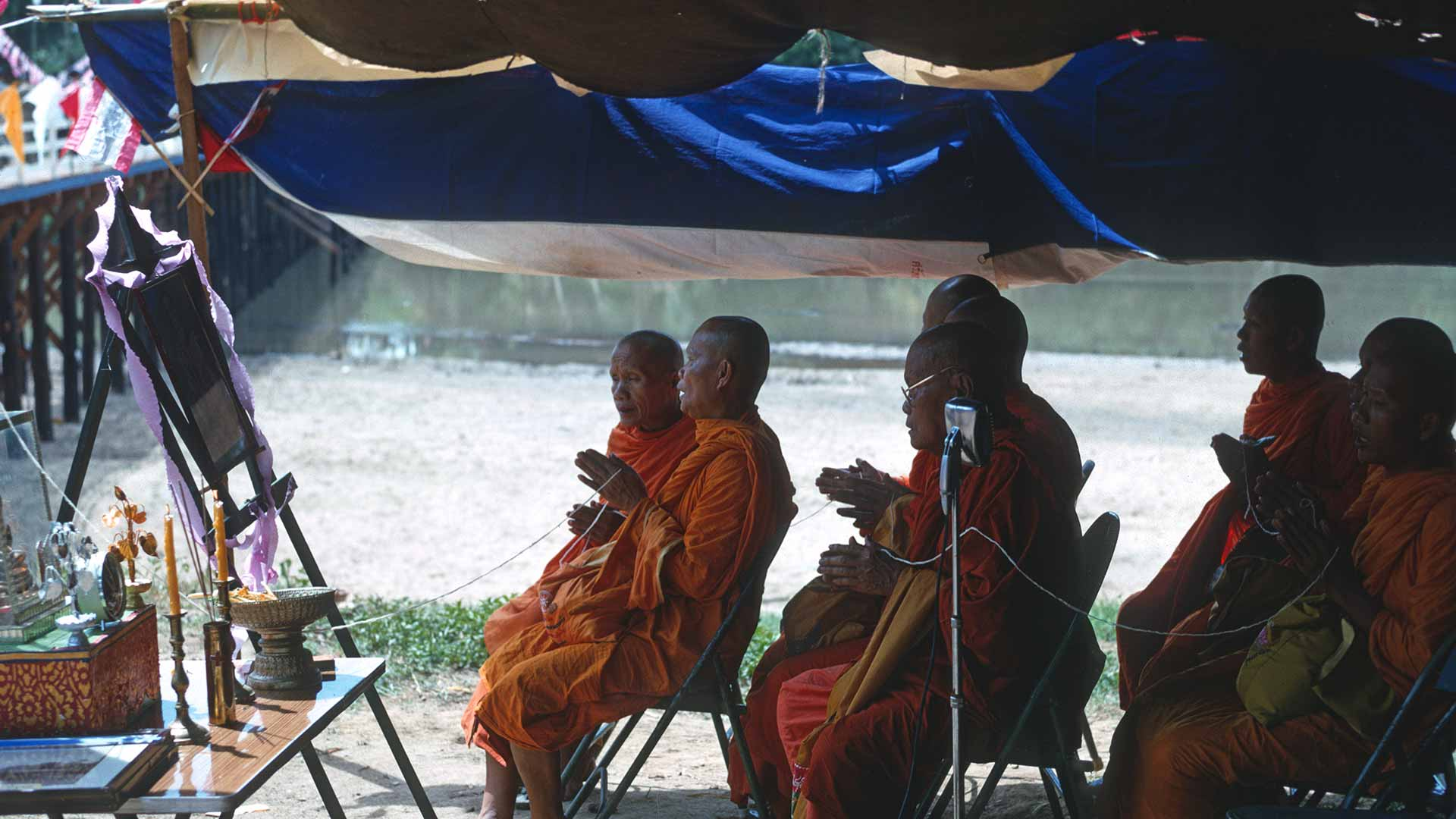 monks sit on folding chairs under a tent and pray to a picture of Buddha.