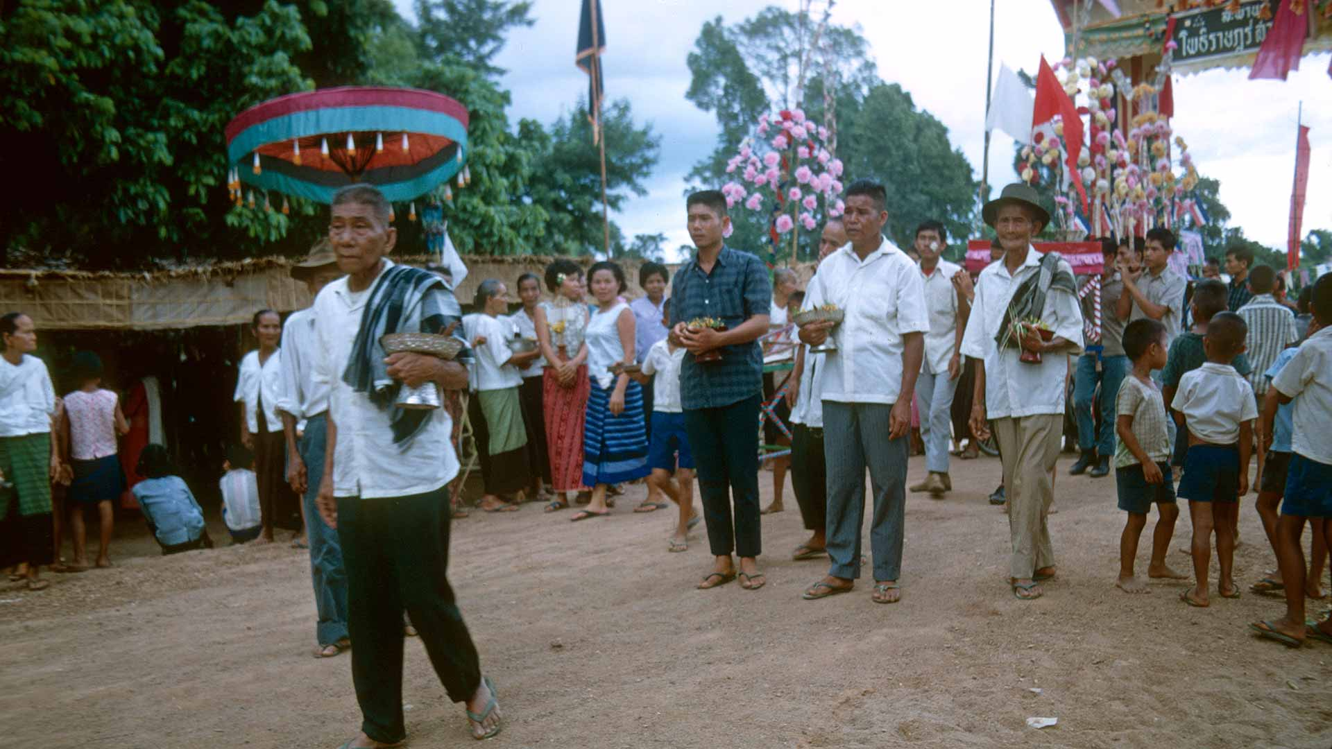 men walk down a dirt road carrying small gifts