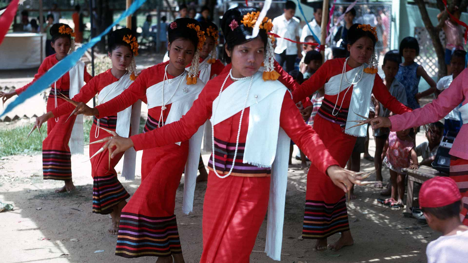 5 women dance in traditional thai red dresses and long golden fingernails