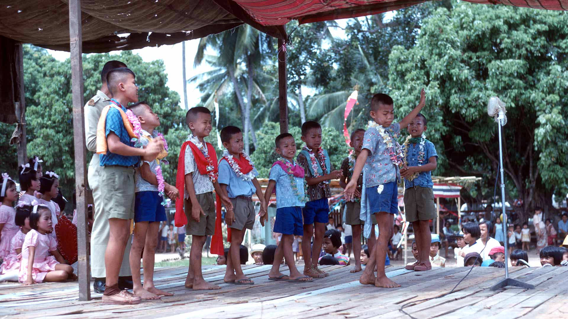boys perform song and dance on a wooden stage