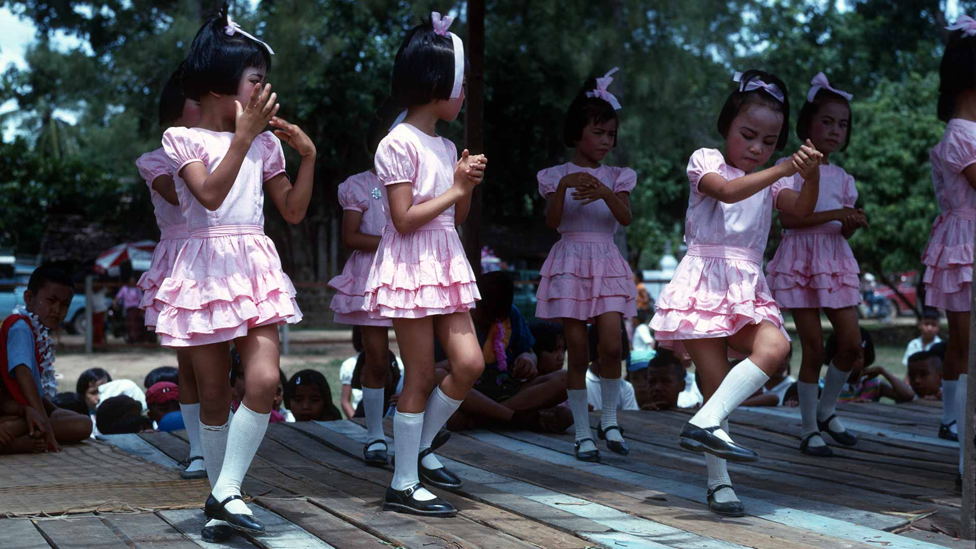 small girls in pink dresses and high white socks dance on a stage