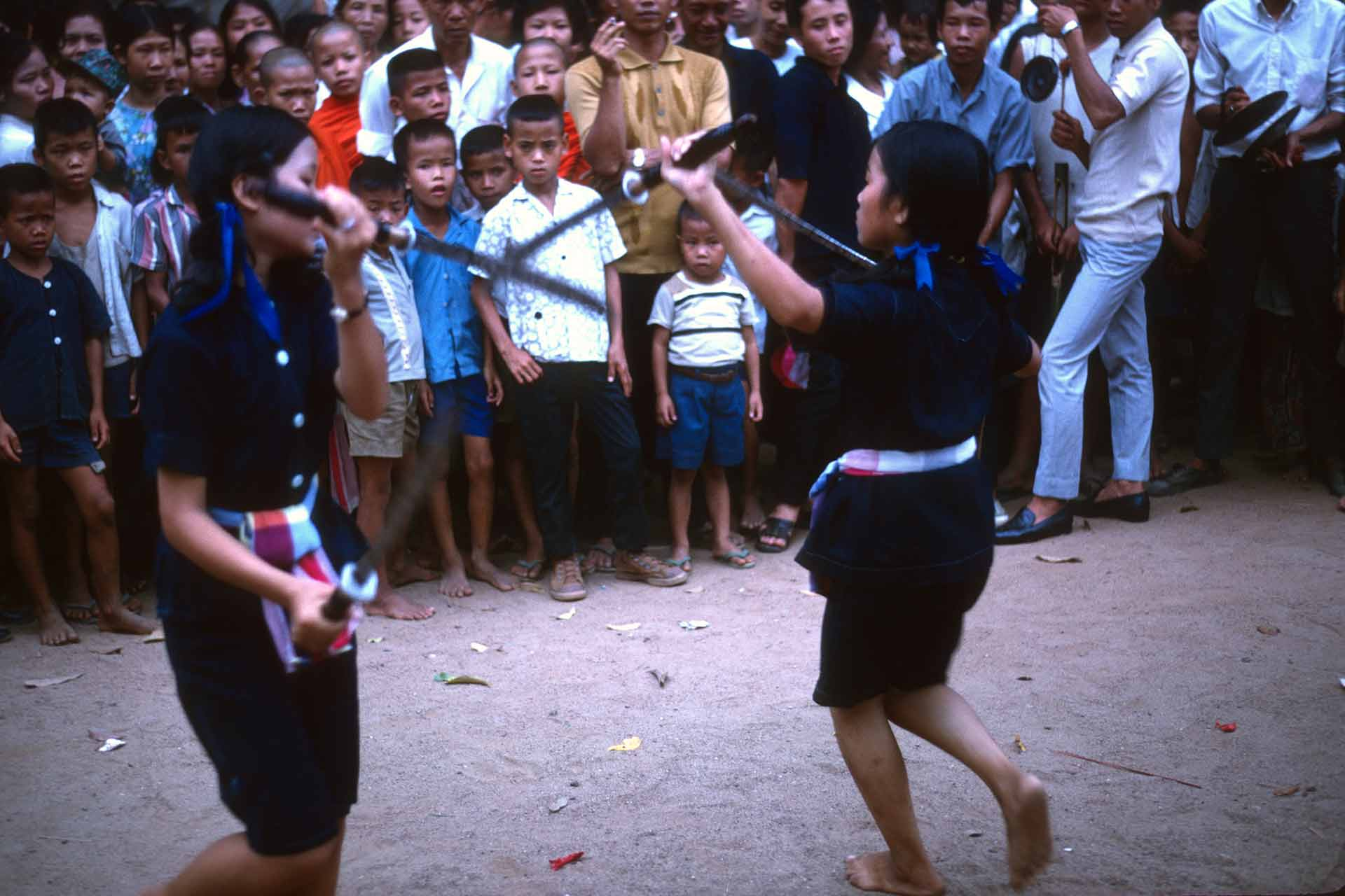 Two girls demonstrate a sword dance in barefoot in front of a crowd