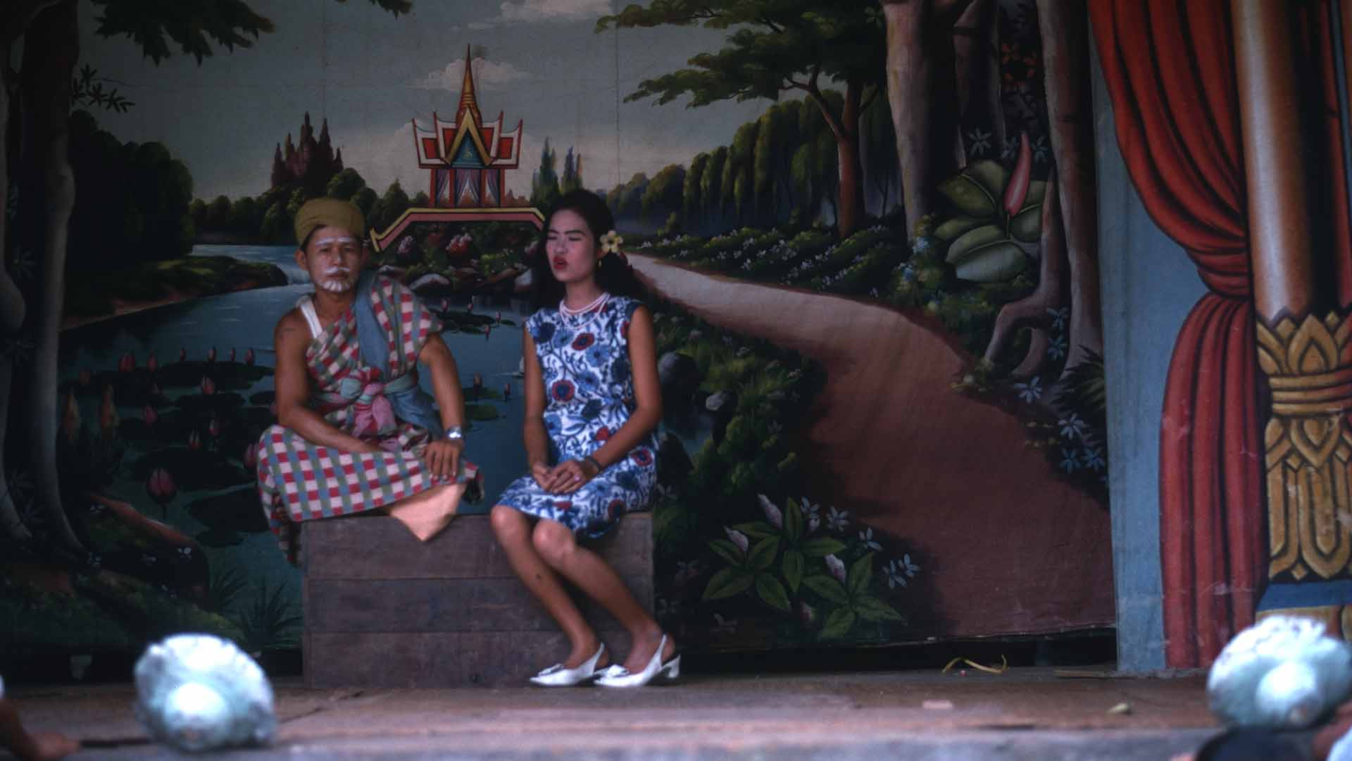 Two actors, a man and a woman, sit on a stage in front of a thai backdrop