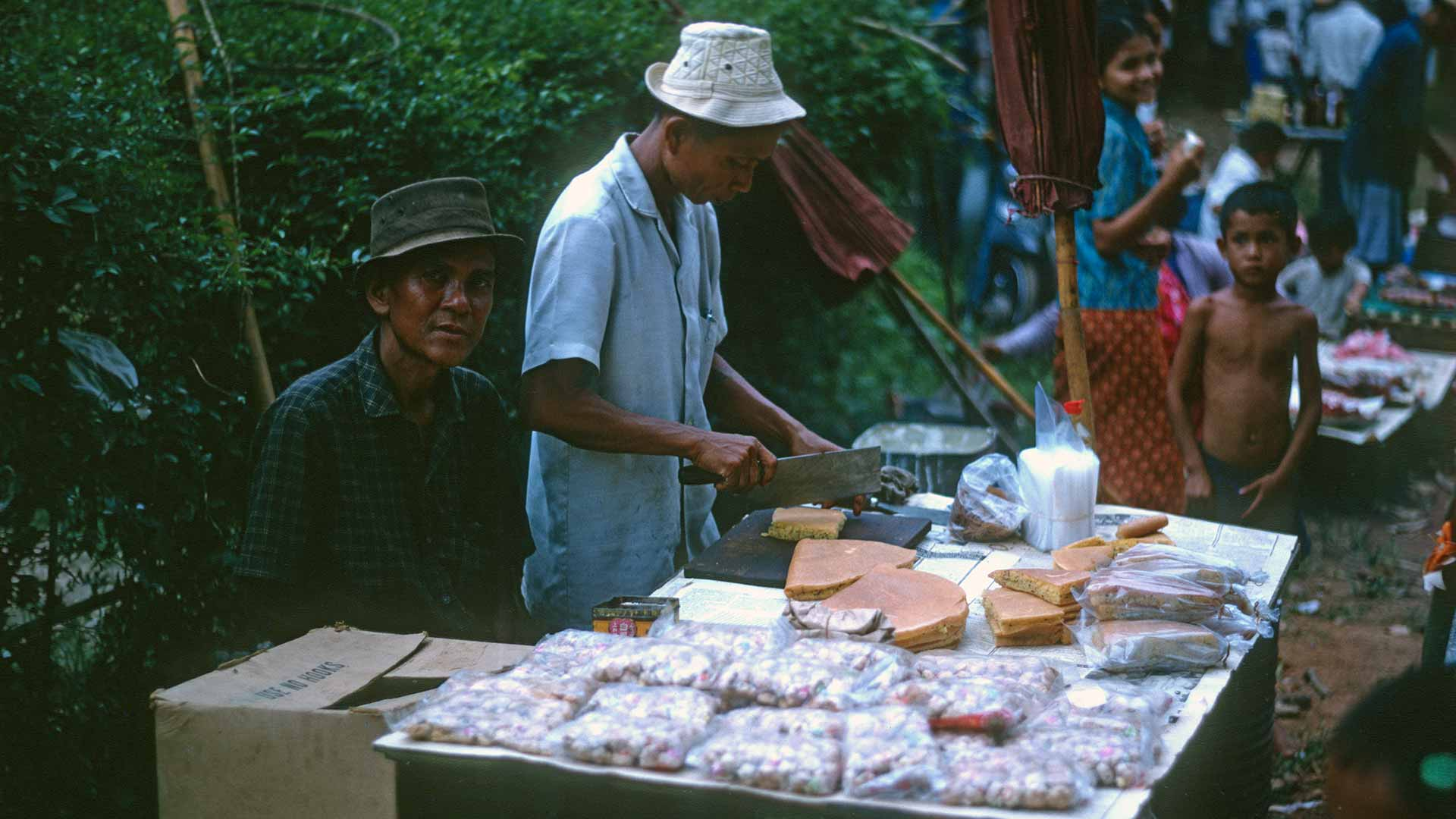 A man prepares food at a table full of food for sale.