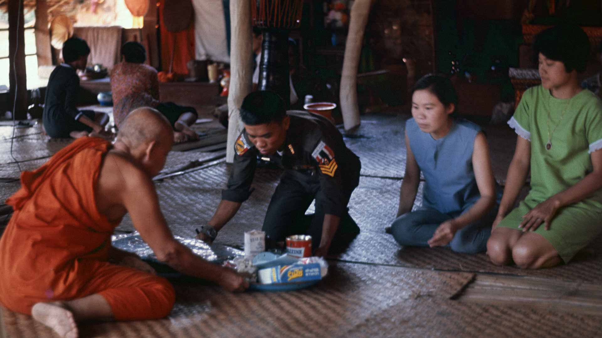 A man in a military uniform pushes a tray of gifts across the floor to a monk