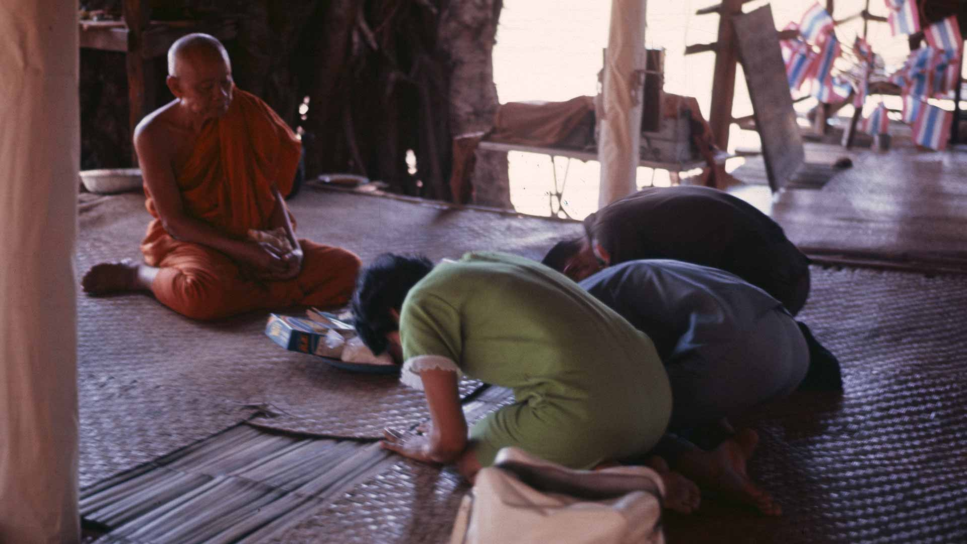 3 people bow their heads and bodies in front of an elder monk