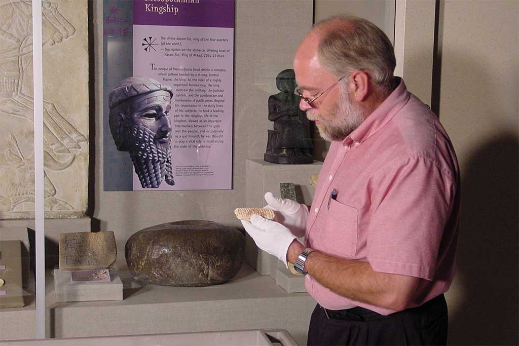 Wayne holds a small cuneiform tablet in front of an exhibit case