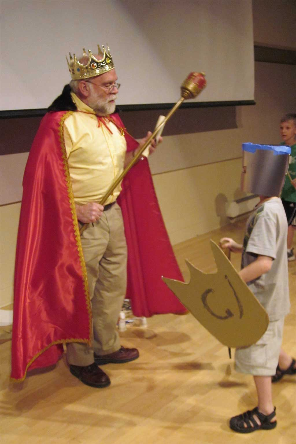 Wayne, dressed as a King, faces a student dressed up as a knight