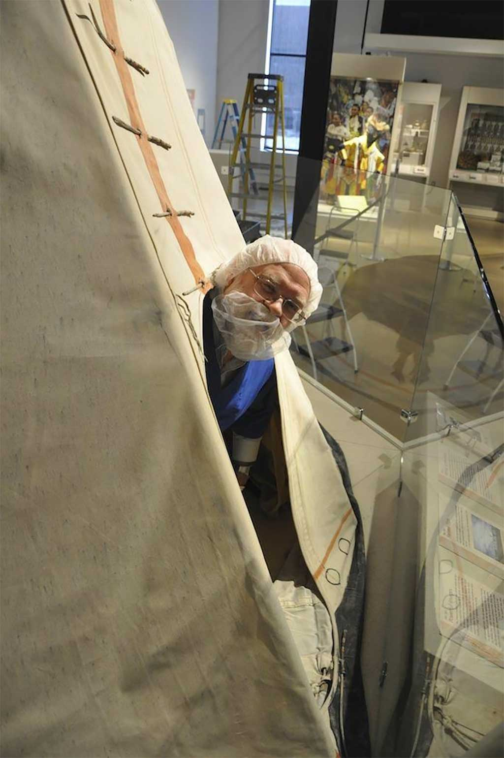 Wayne pops his head out of the tipi in the exhibit gallery