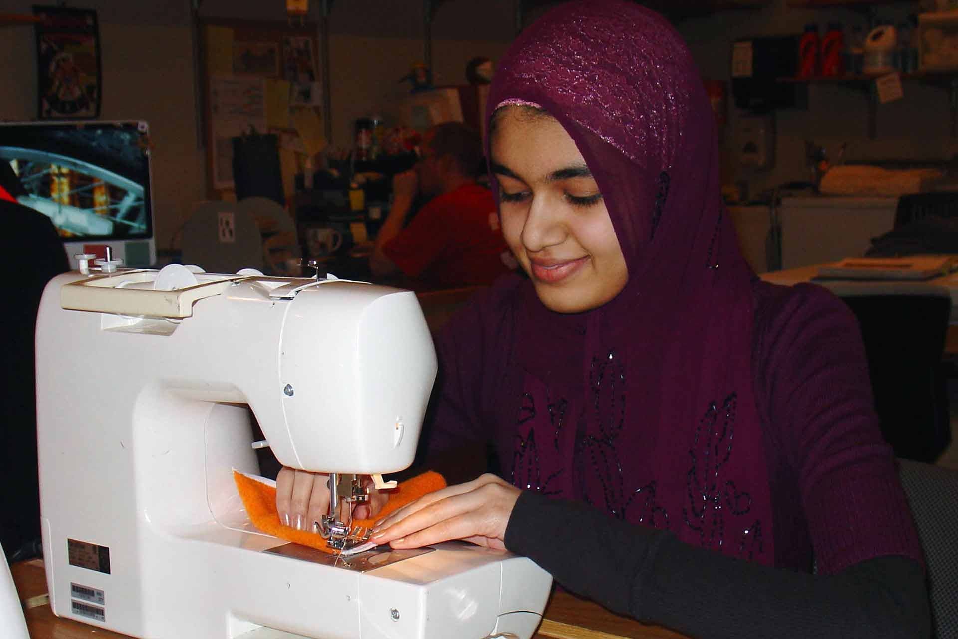 close up of a smiling student using sewing machine to sew fabric