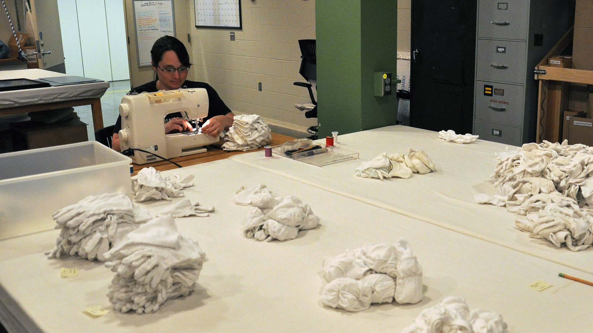 A student uses sewing machine to sew piles of gloves