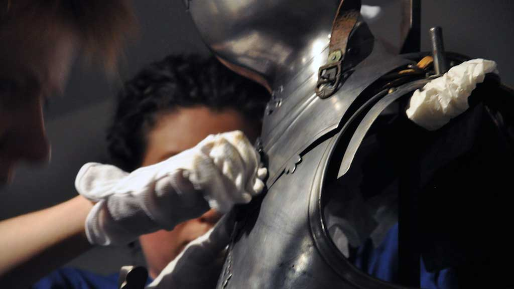 two staff members remove the armor from exhibit