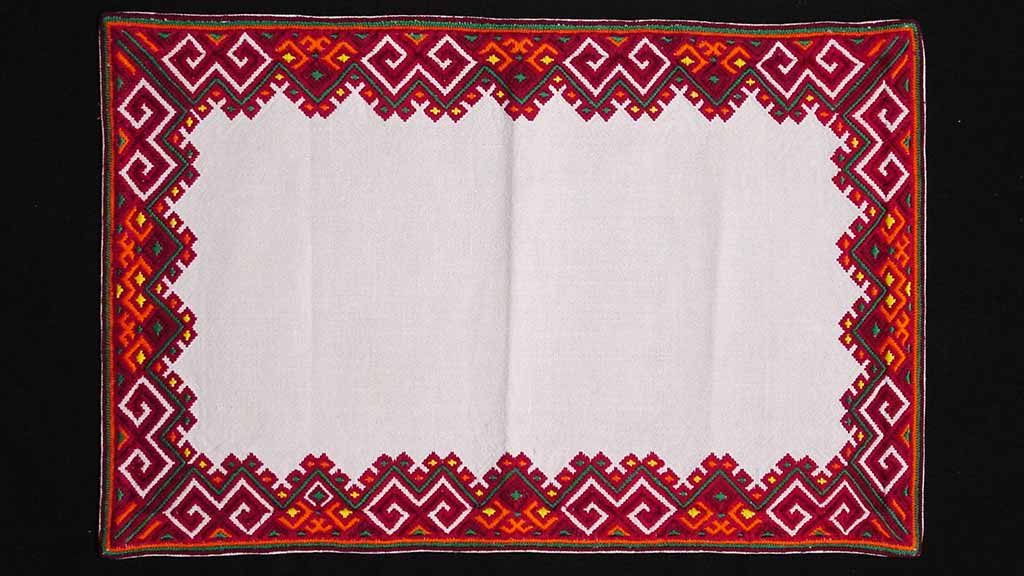 white cloth with red geometric border