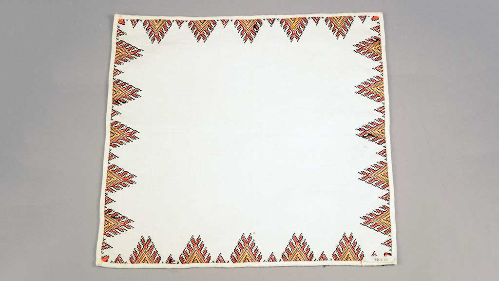 white cloth with red and yellow pointed border