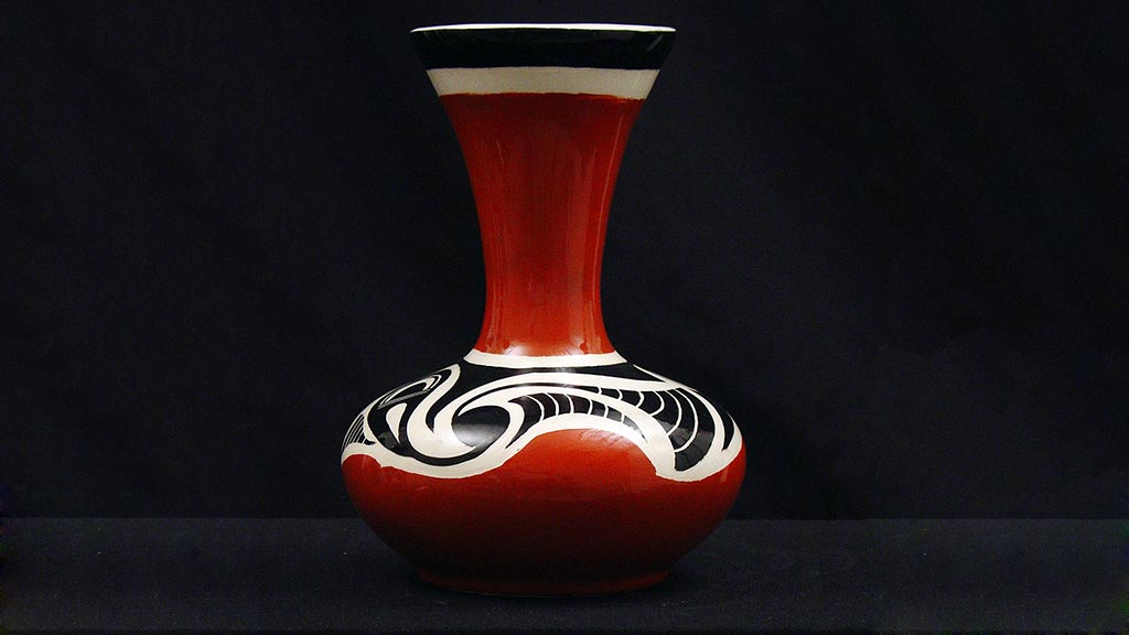 red, black, and white vessel with wide base