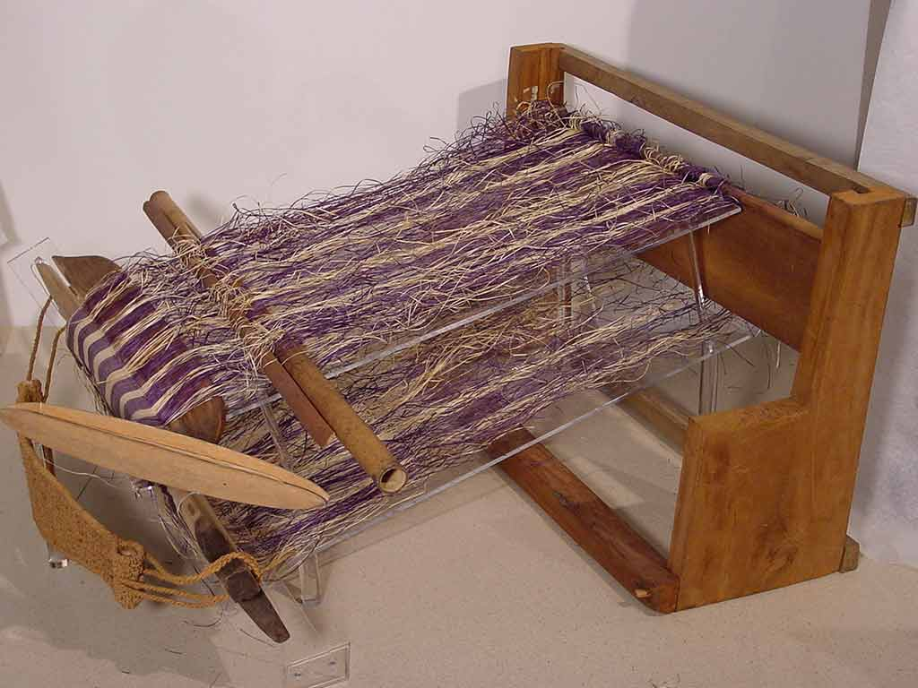 wooden loom with partially completed purple and tan textile