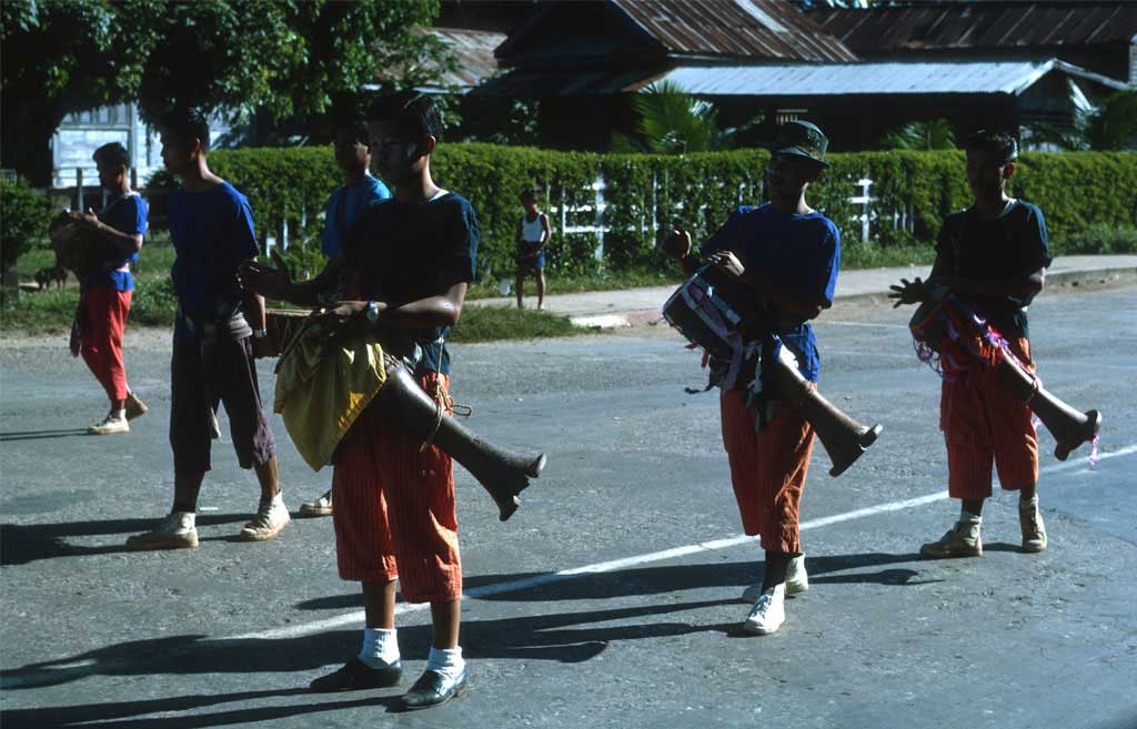 Boys walking down the street while playing drums on their way to the temple