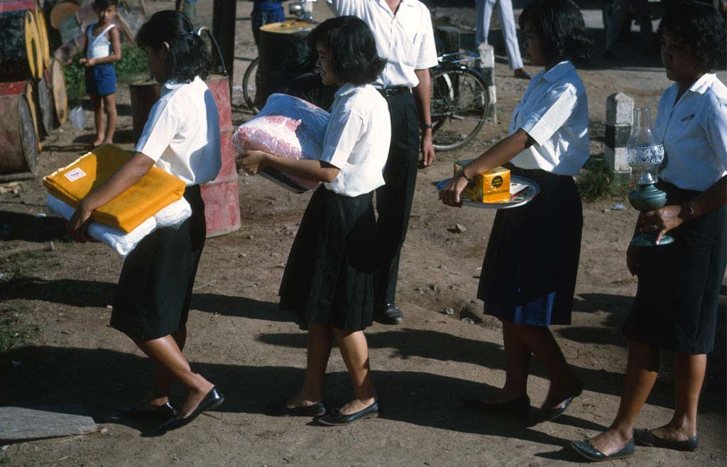 A group of school girls walking to the temple carrying gifts for the monks.
