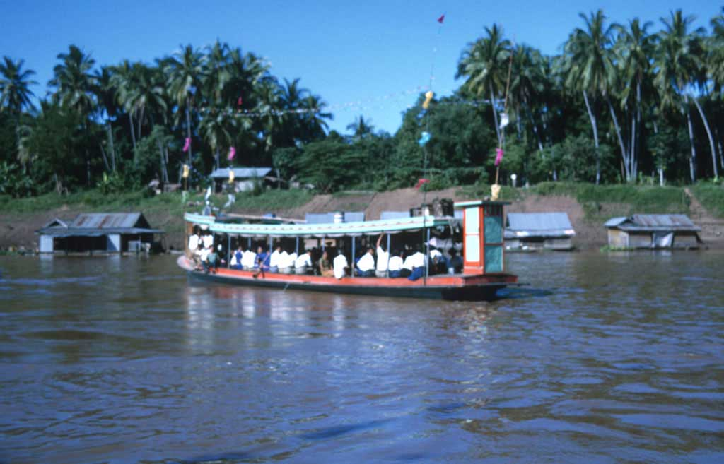 A large decorated boat filled with people on a river.
