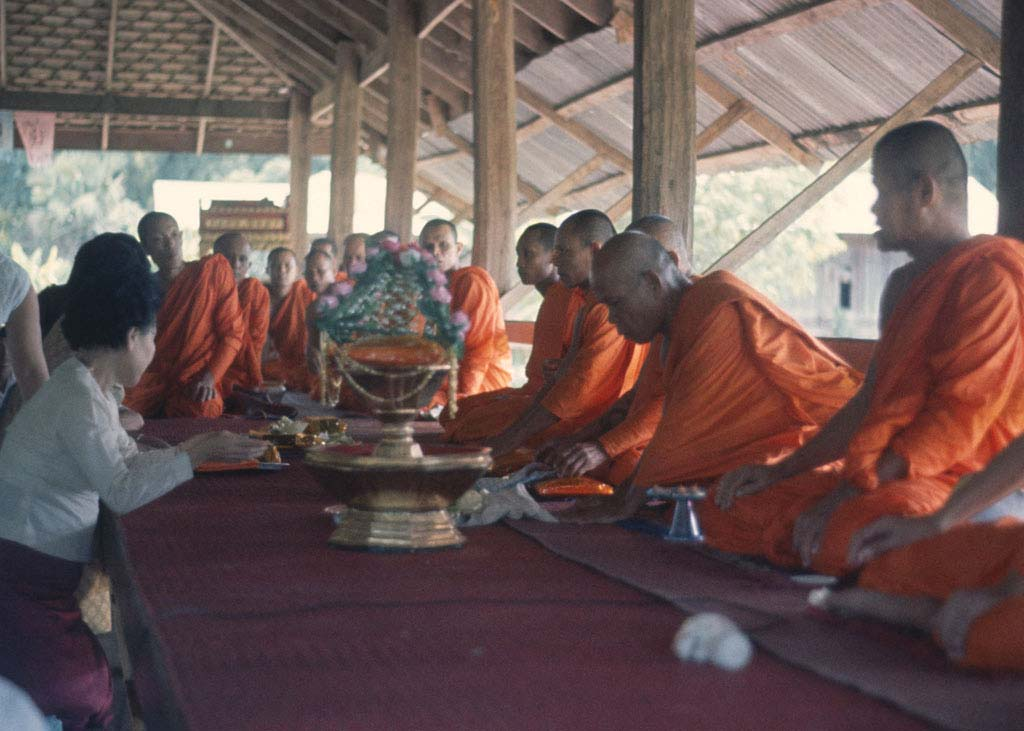 Monks sit attentively as gifts are being presented
