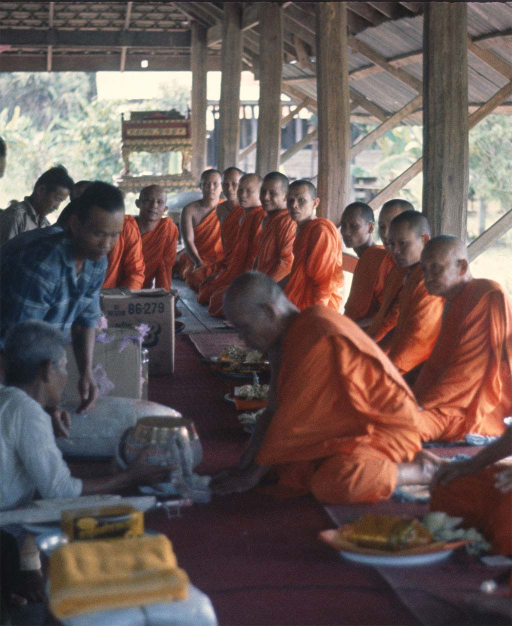 A group of monks are seated around one monk participating in a presentation of gifts