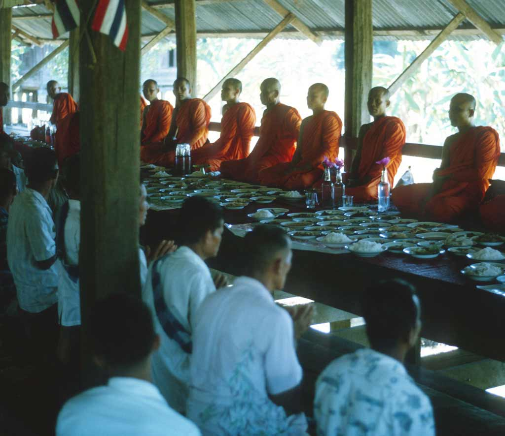 Monks are seated on one side of a long table and villagers are on the other side kneeling and waiting for the monks to begin eating