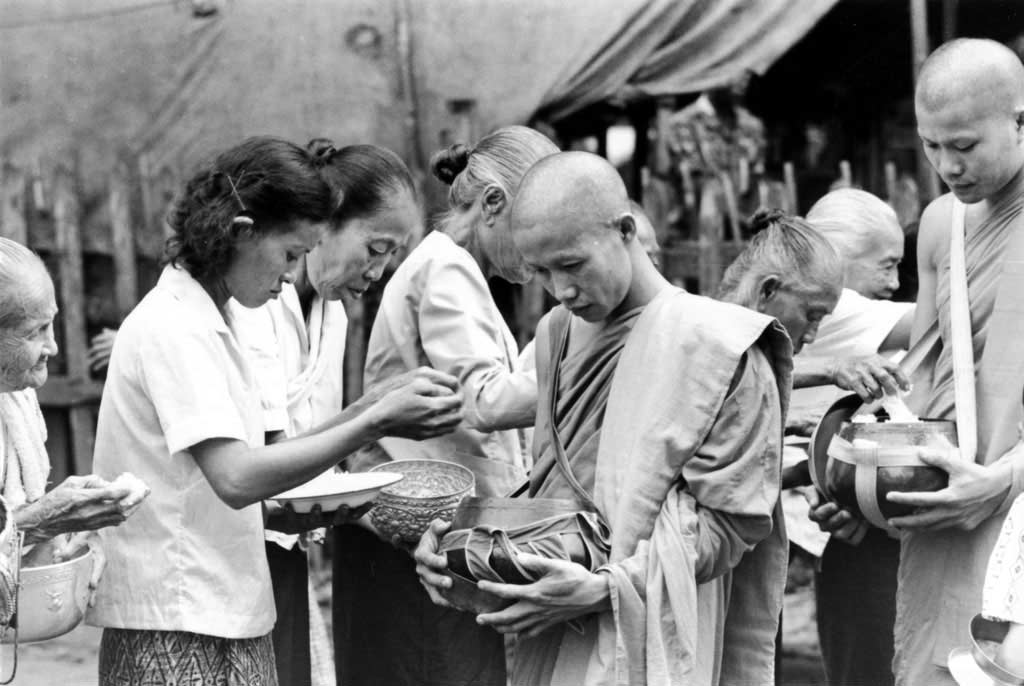 Women filling monk's bowls with rice