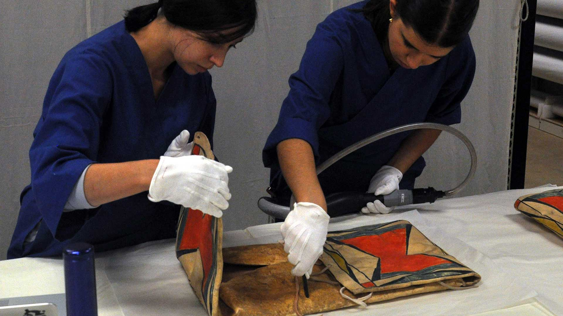 Two collections students vacuum a parfleche bag